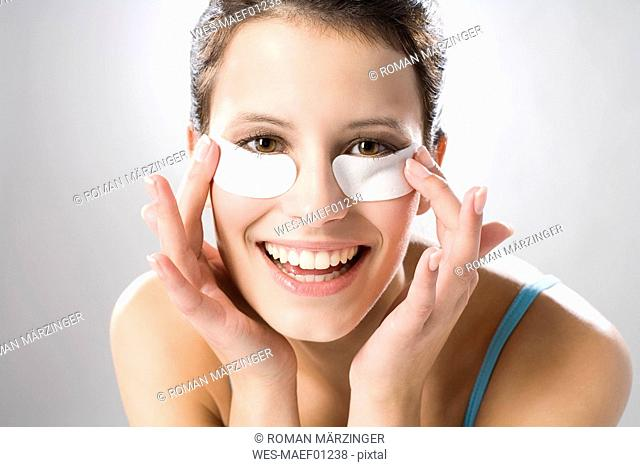 Young woman using eye pads, smiling, close up
