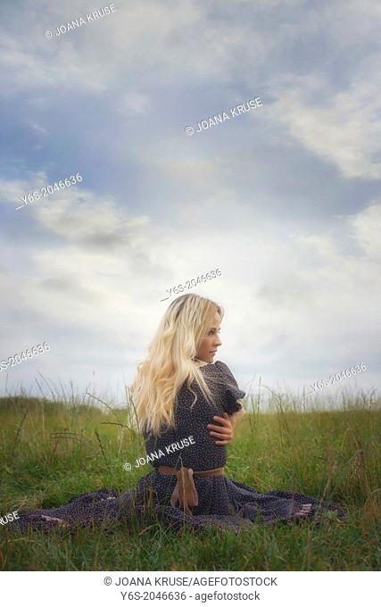 a girl in a romantic dress is sitting in the grass, hugging herself