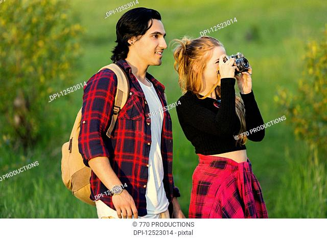 Young couple walking together in a city park pause to take a picture with a camera; Edmonton, Alberta, Canada