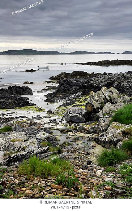 Sand beach and rocky shore and clouds on Isle of Iona with boat on Sound of Iona past Isle of Mull in Inner Hebrides Scotland UK