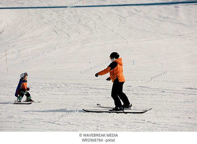 Little boy learning to ski with instructor on snowy slope