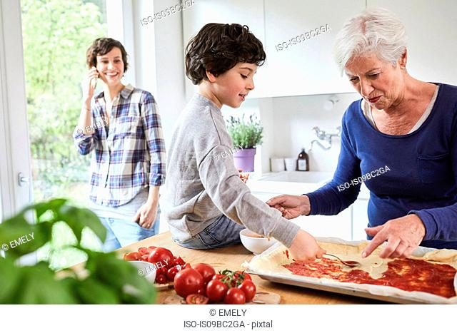 Grandmother and grandson making pizza in kitchen, mother in background using smartphone