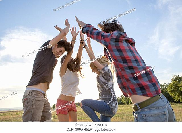 Four friends jumping with arms raised