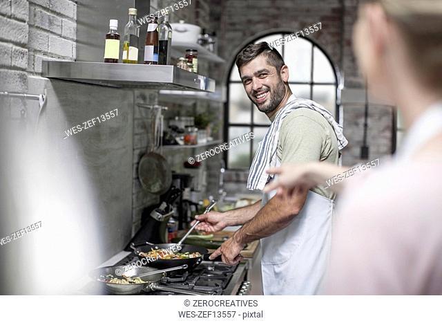 Smiling man preparing meal looking at wife