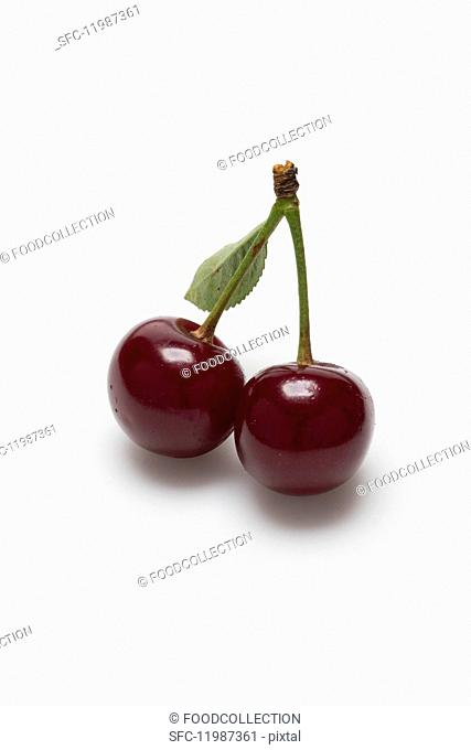 Two sour cherries on a white surface