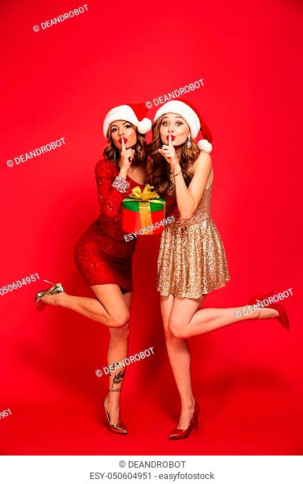 Full length portrait of two attractive young women in christmas hats holding present boxes while showing silence gesture and looking at camera isolated over red...