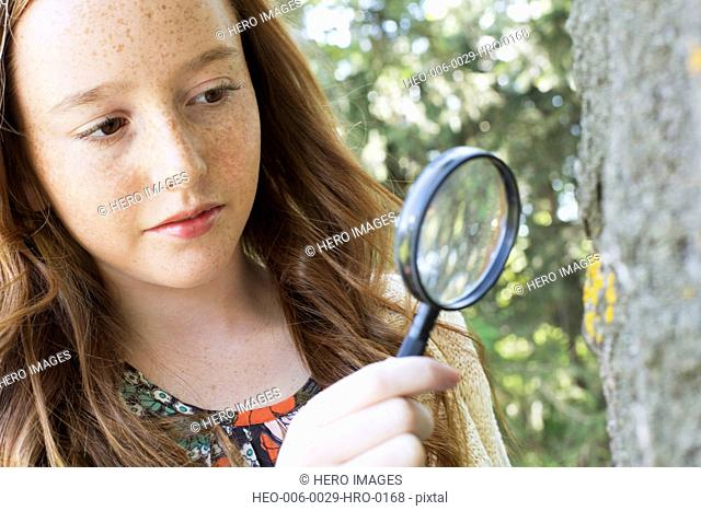 female middle school student looking through a magnifying glass