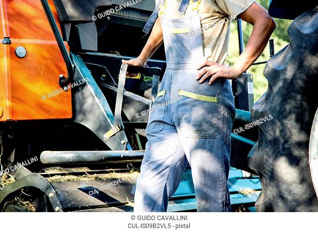 Mid section of male farmworker leaning against tractor