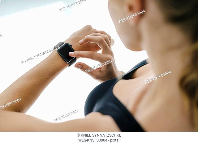 Close-up of woman in sportswear adjusting her smartwatch