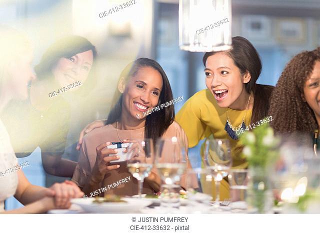 Smiling women friends celebrating birthday at restaurant table