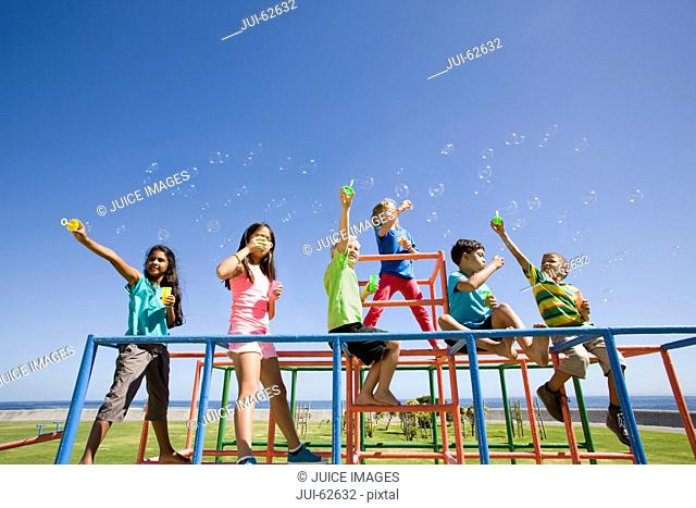 Children blowing bubbles on monkey bars at playground