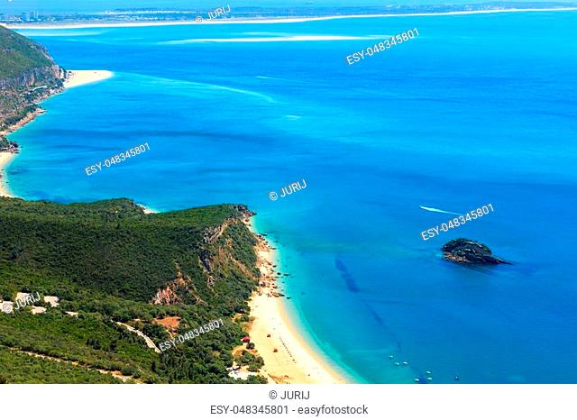Summer sea coastal landscape with sandy Portinho beach. Top view from Nature Park of Arrabida in Setubal, Portugal. All peoples unrecognizable