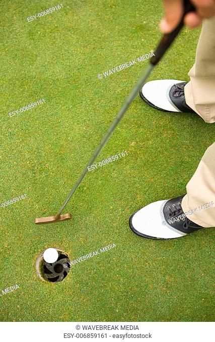 Golfer putting golf ball in the hole
