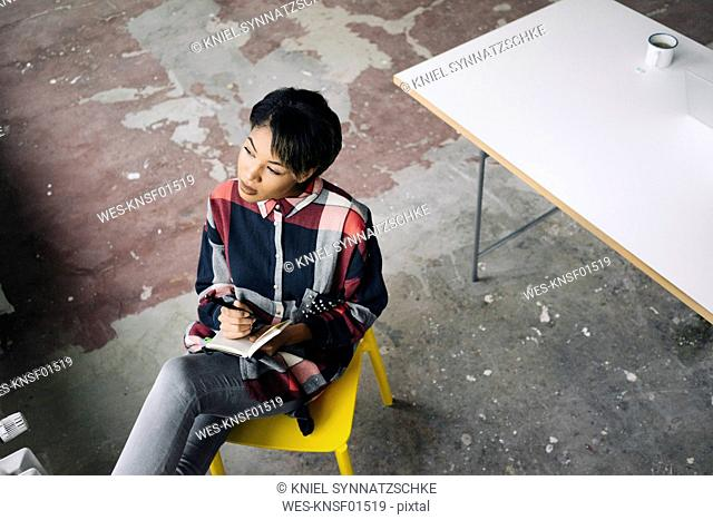 Woman sitting on chair with notebook