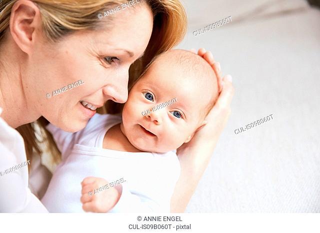 Mid adult woman cradling baby daughter