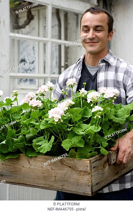 Portrait of a smiling middle-aged man carrying flowers