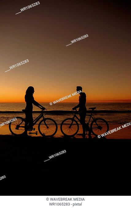 Silhouettes of people facing each other on bikes