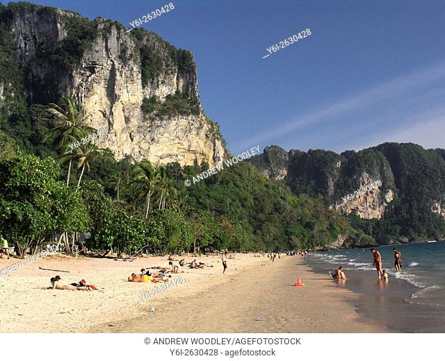 Limestone cliffs tower over the palms and sand Ao Nang beach near Krabi Thailand