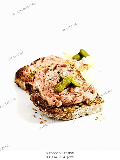 A slice of toast topped with chicken liver pâté and gherkins
