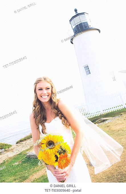 Portrait of smiling bride holding sunflower bouquet, lighthouse in background