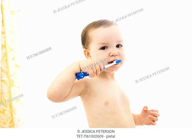 Shirtless boy (4-5) brushing teeth