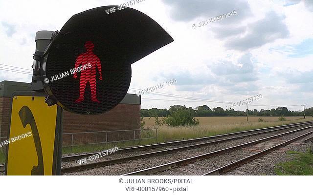 Pedestrians do not cross - red flashing man as a passenger train passes 4:2:2