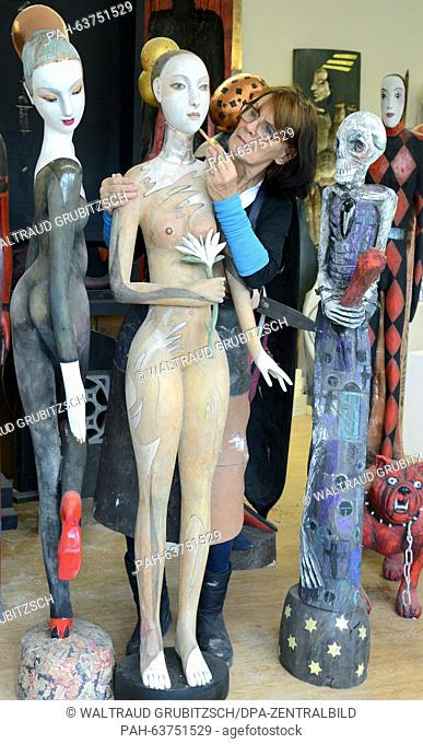 The sculptress Gabriele Messerschmidt in her studio in Leipzig, Germany, with her wooden sculpture 'Jagerin am Rande der Nacht' (lt: Huntress makes her nightly...
