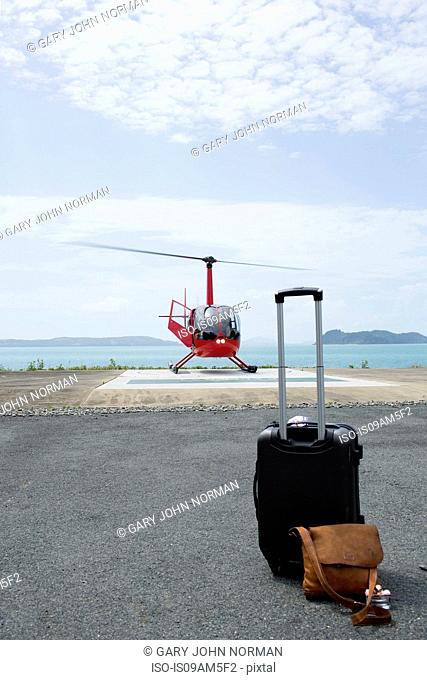Luggage in front of helicopter preparing to leave from Long Island, Whitsunday Islands, Queensland, Australia