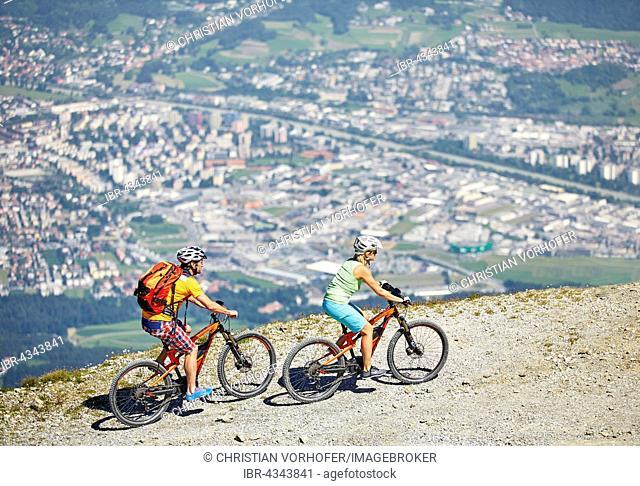 Man 40-45 years and woman 35-40 years with helmets cycle with their mountain bikes, Zirbenweg, Patscherkofel, Innsbruck, Tyrol, Austria
