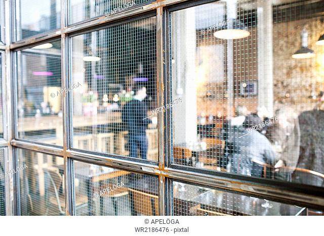 People in cafe seen through glass window