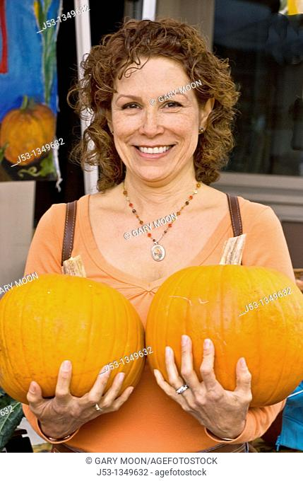 Woman holding two pumpkins at farmers' market, Nevada City, California