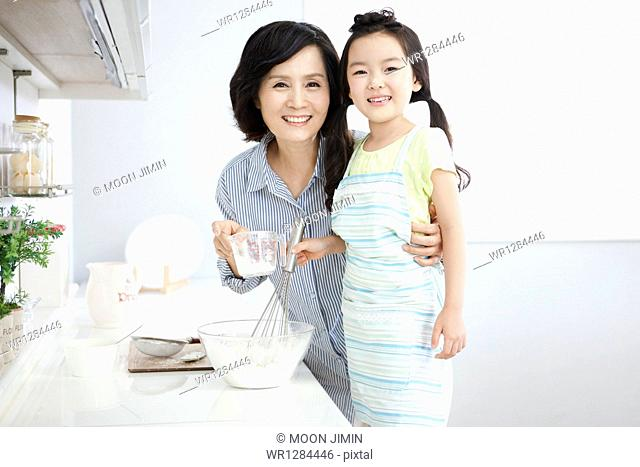 a mother and a daughter cooking together
