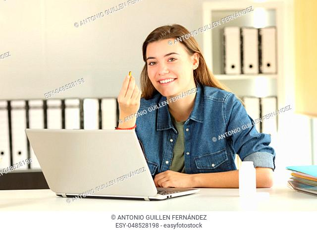 Happy intern showing a vitamin pill sitting in a desktop at office