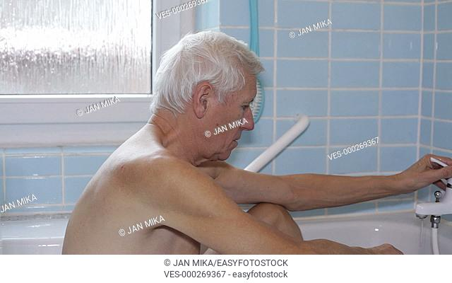 Senior man sitting in bath and using shower