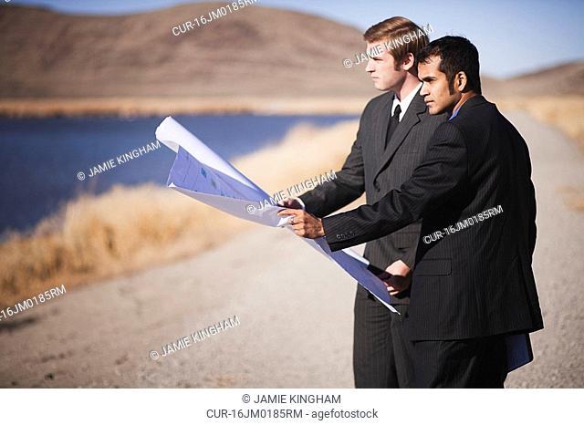 2 men with blueprints looking over water