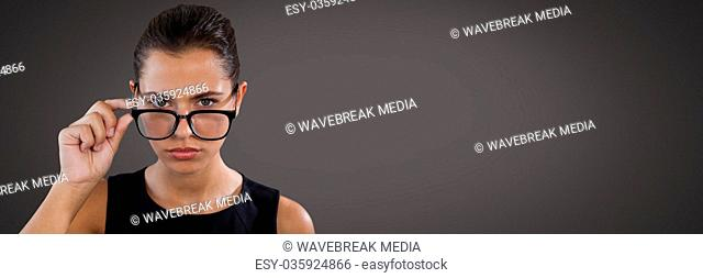 Businesswoman thinking and peering over glasses with dark background