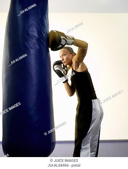 Portrait of a female boxer punching a punching bag