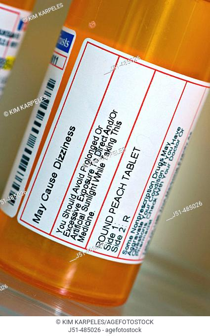 STILL LIFE. Riverwoods, Illinois. Close up of pharmacy label, warnings and precautions, bottle of prescription drug on shelf, bathroom medicine cabinet