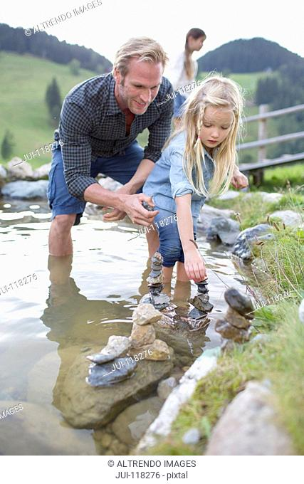 Father And Daughter Playing With Stones In Stream
