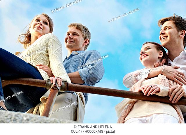 Couples standing at railing outdoors
