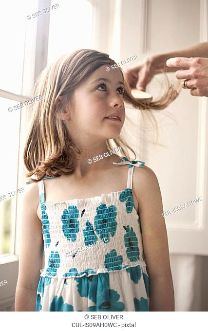 Girl having her hair brushed by her mother
