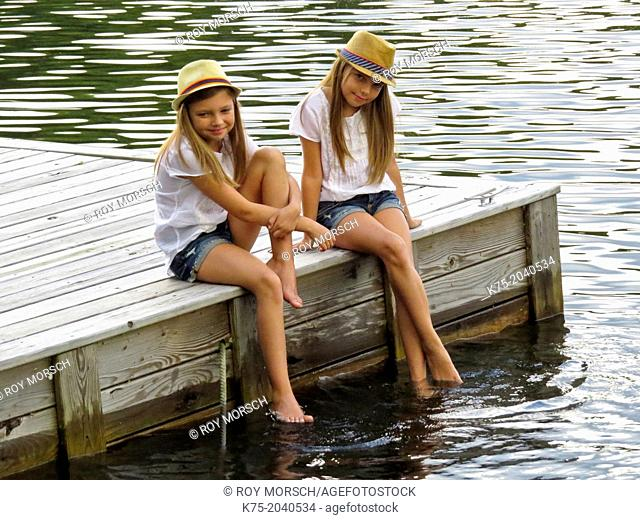 Twin sisters sitting on a dock on a lake