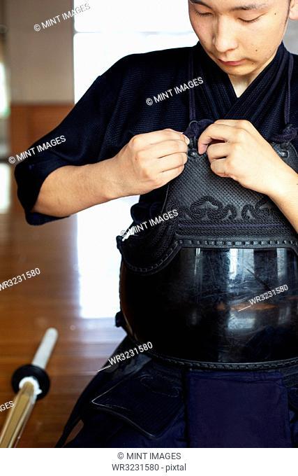 Male Japanese Kendo fighter kneeling on floor, fastening his breastplate