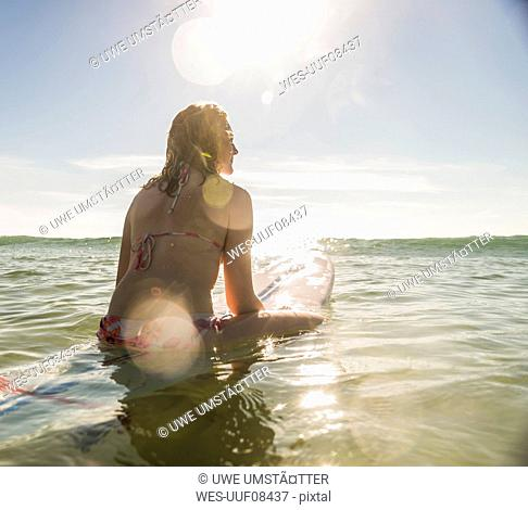 Teenage girl with surfboard in the sea