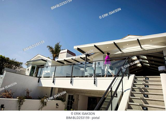 Hispanic woman walking on modern balcony