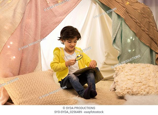 boy with magnifier and map in kids tent at home
