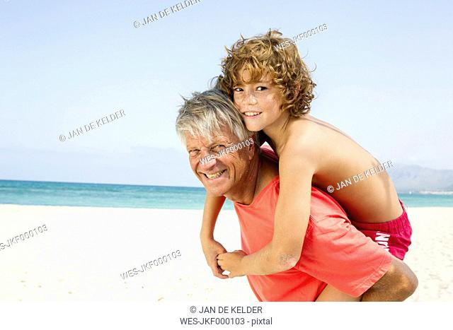 Spain, Grandfather giving piggyback ride to grandson, smiling