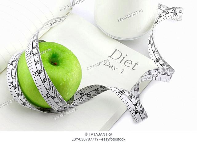 Green apple on a notebook and measuring tape, Diet concept