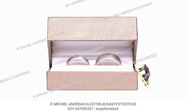 Wedding rings in box, small man climbing into the box, isolated on white background
