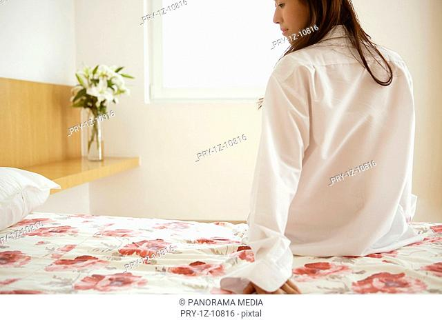 Young woman leaning on bed